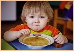 Смешной мальчуган ест суп