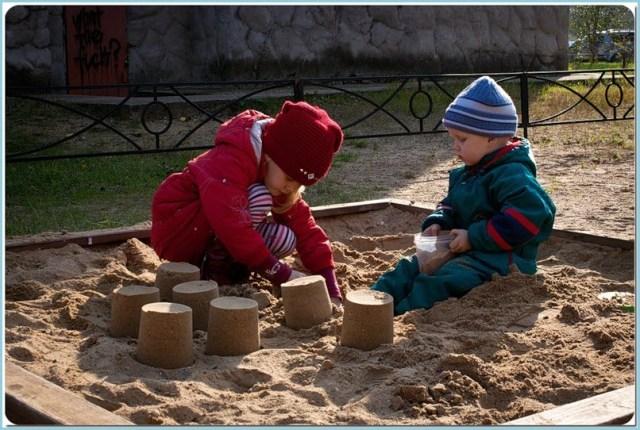 Дети делают куличи из песка