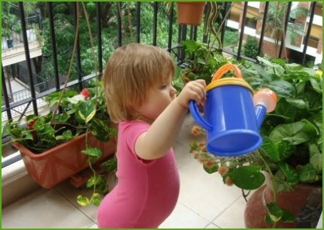 На фото девочка поливает цветы