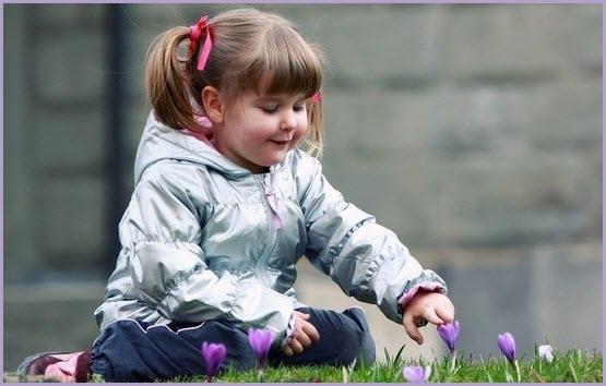 На фото девочка и первоцветы