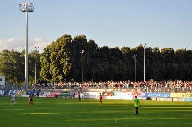 Zuschauer auf der sonnigen Gegentribüne in der Memminger Arena