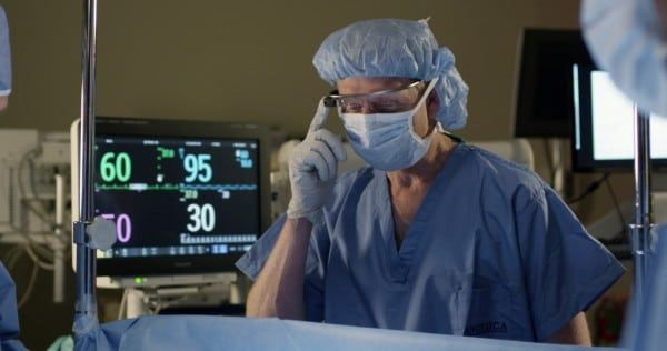Anesthesiologist viewing vital signs during surgery