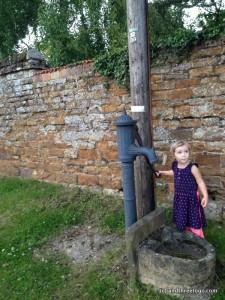Zoë trying to get water from the town water pump.