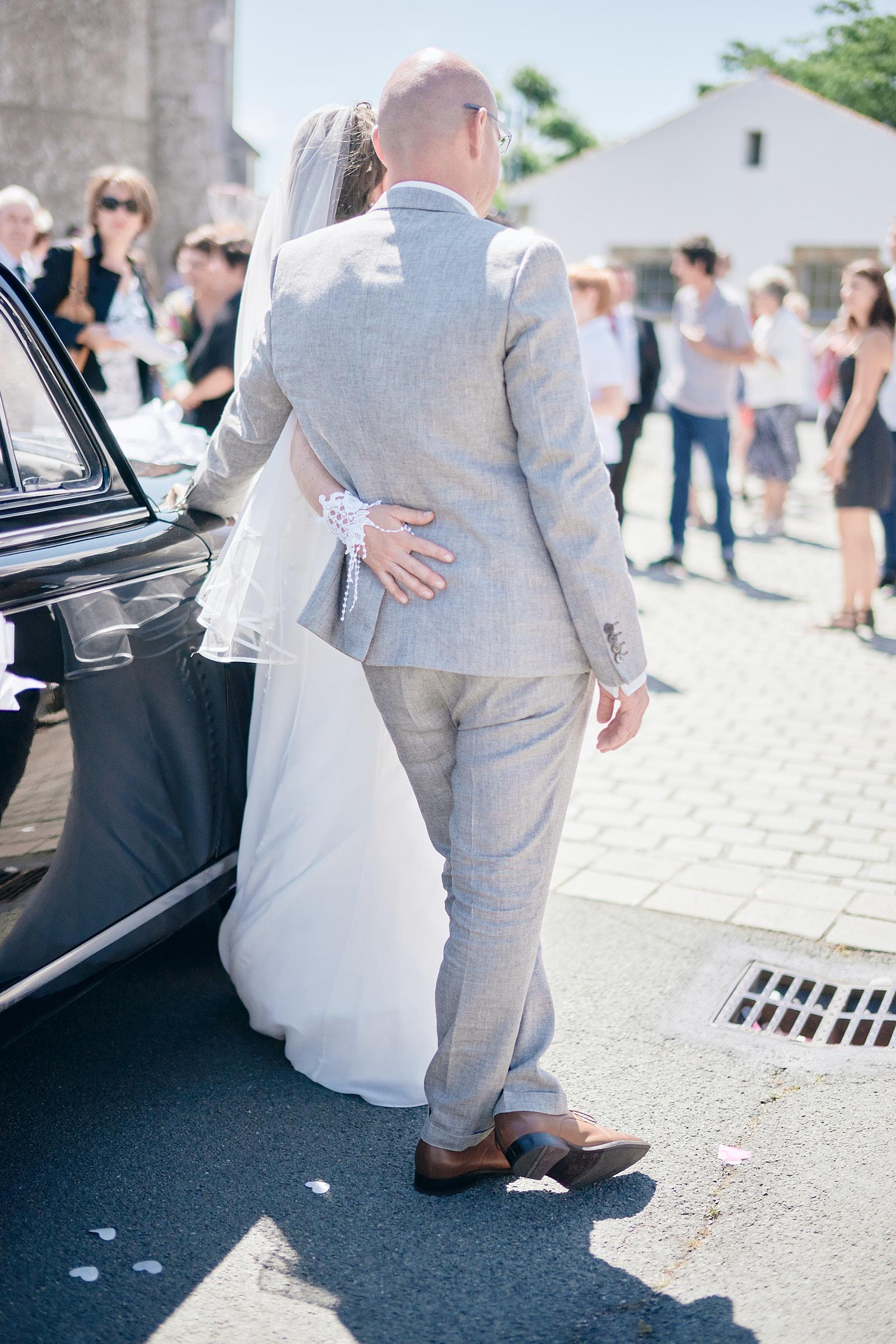 les mariés de dos appuyés sur le véhicule de collection en vendée