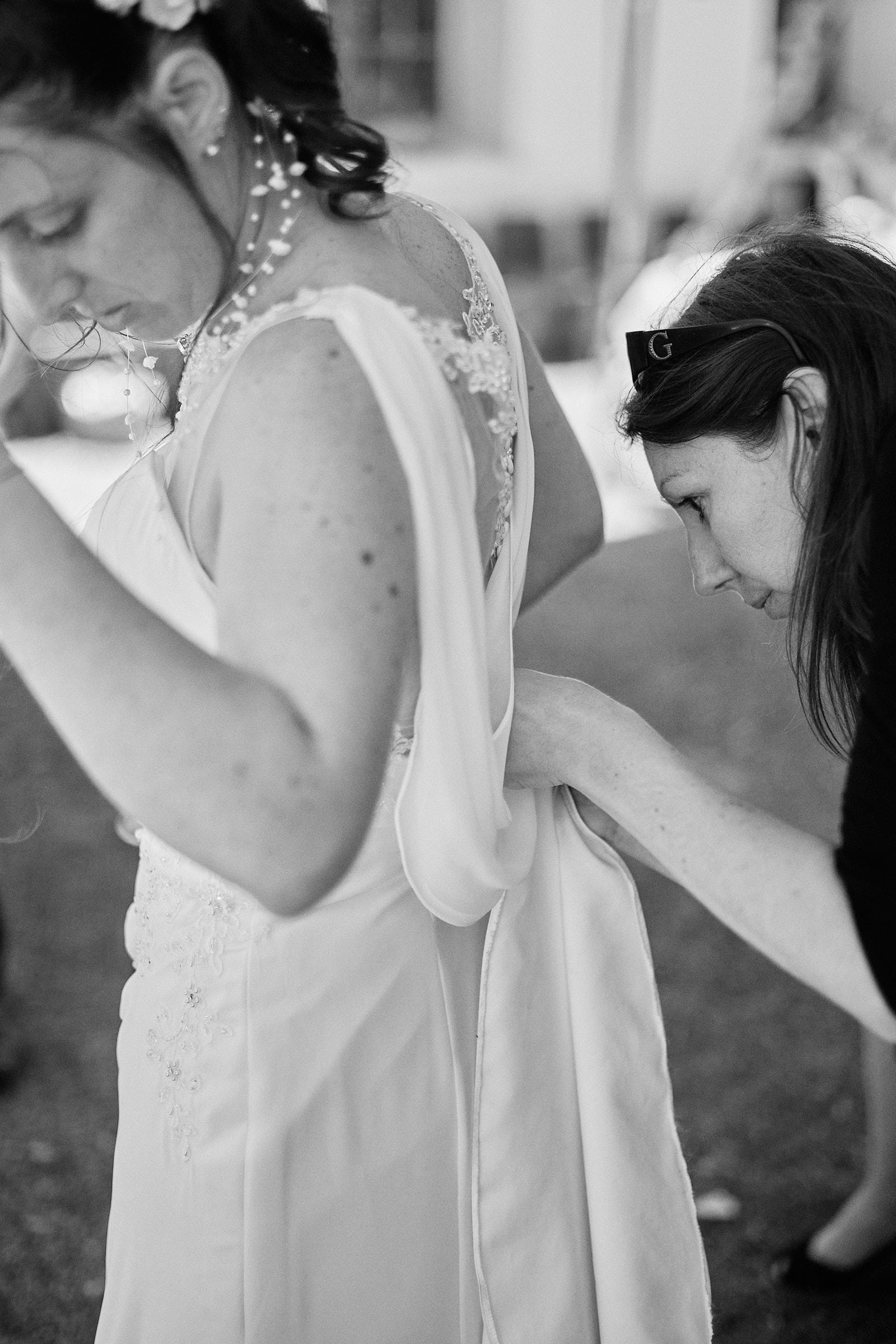 une amie attache la traîne de la mariée