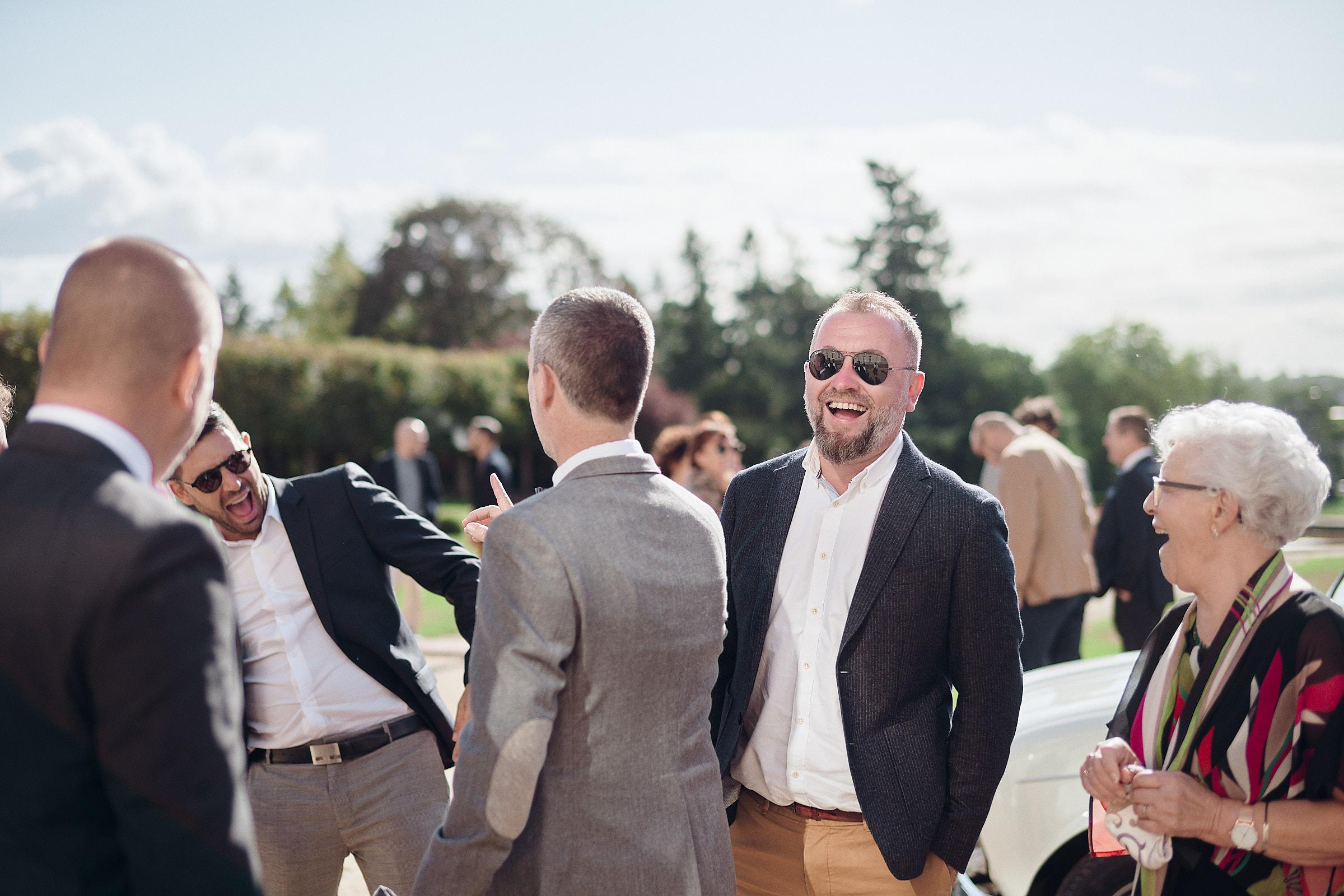 les invités rigolent avec le marié sur la terrasse sud du chateau de craon
