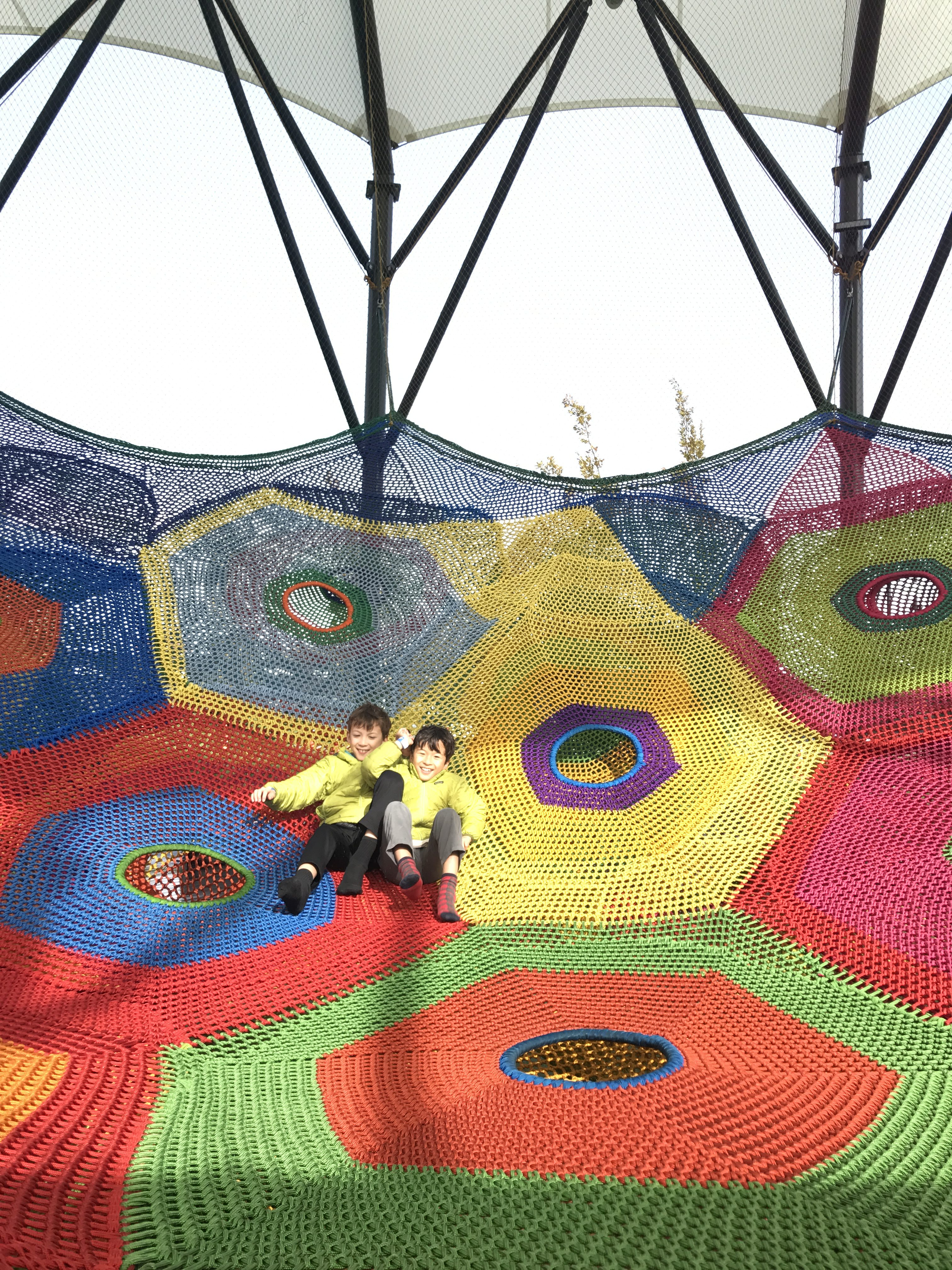 Hanging out in the rain at the Crocheted Net Playground at Whoa Studios in New Zealand with kids