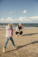 blondes Mädchen läuft am Strand von Usedom auf ihre hockende Mutter zu