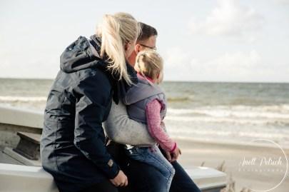 Familie sitzt auf dem Rand eines Boots und schaut Richtung Ostsee