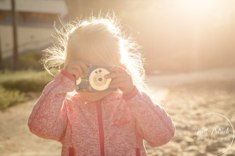 Kleines blondes Mädchen hält eine Kamera vor dem Gesicht