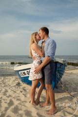Pärchenfotos am Strand von Usedom, das Paar steht vor einem Fischerboot und küsst sich