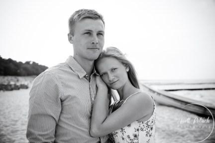 schwarz weiß Paarshooting am Strand die Frau lehnt an der Schulter des Mannes und schaut direkt in die Kamera, der Mann guckt auf das Meer