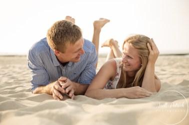 Pärchen liegt auf dem Bauch am Strand und schaut sich verliebt an