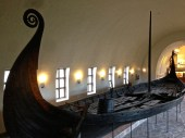 Looking down into the Oseberg, you can see the deck, gangway, rudder/tiller, and a bailing bucket.