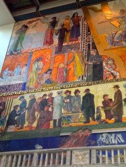 On the left side, at the very bottom below the figures, we see flames destroying Vika, the slum that was razed to make room for City Hall. The fiery scene not only calls to mind the many blazes that once plagued the wooded-shantied ghetto, but also refer to the social revolution avoided by creating better living conditions for its residents. The line of folks above the fire are all responsibly participating in local government and laboring to rebuild the city. Above them, we see healthcare being provided to mothers in Oslo's new Maternity Ward, and children receiving free education in public schools.