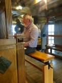 You can see just the ends of the little wooden levers that stick out of the carillon. The man strikes these with the edge of his fists, using them like hammers. His feet get in on the action, too, by stamping out some of the deeper notes on pedals.