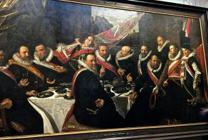 """The """"Banquet of the Officers of the St. George Civic Guard"""" has that characteristic lifelike trademark of Hals' work. You feel as if you've just interrupted the frat boys at their kegger. And from the mocking looks on their faces, they're not particularly impressed with you. The Civic Guards were wealthy merchants, bankers, and tradesmen who'd been elected by citizens to protect the city in case of attack. Methinks meetings were mostly an excuse to party. Hals, Rembrandt, and other Dutch Masters painted lots of Civic Guard portraits during their careers."""