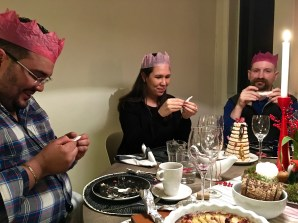 """The almond-flavored Kransekake (""""wreath cake"""") comes with candies and British crackers pinned to it. So we played the traditional game of snapping open the crackers with a communal tug, then donning the crowns and reading the jokes hidden inside. Only one problem. The jokes were in Norwegian, so we had to do some creative translating."""