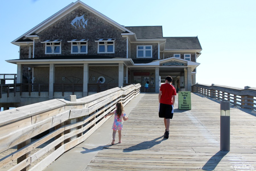 Two kids walking into Jennette's Pier, Nags Head, NC