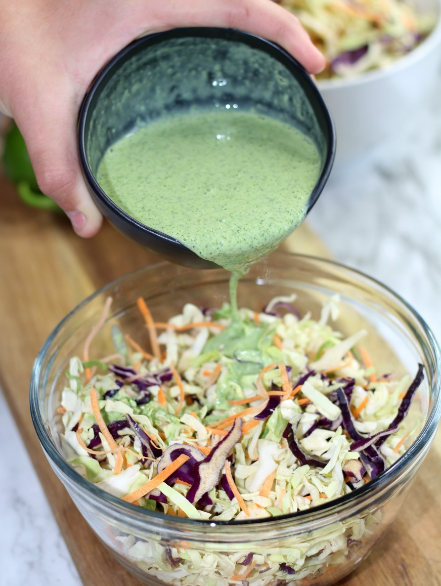 Pouring Cilantro Lime dressing on coleslaw