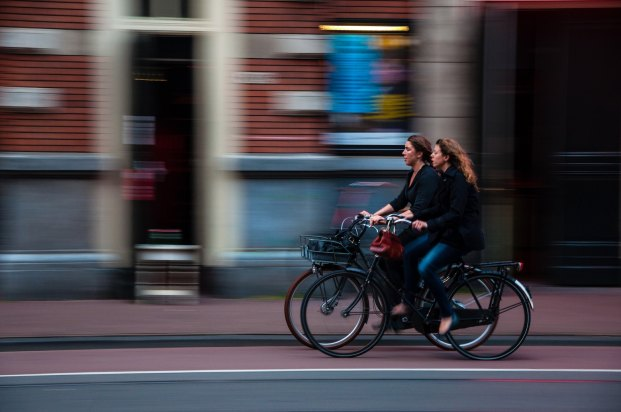 2 women riding bicycle in a city