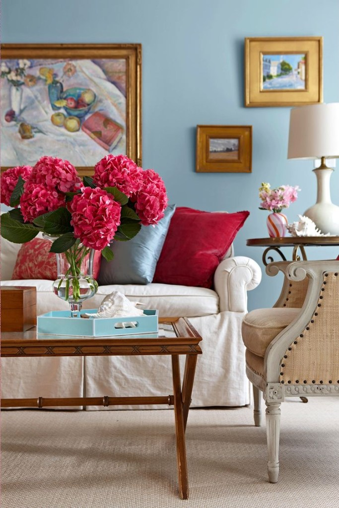 Light blue living room with pink pillows by Michael Partenio