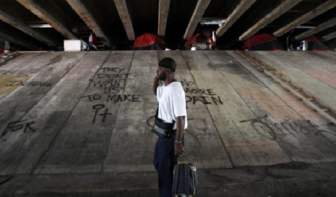 Un homme afro-américain sur la trentaine, pauvrement vêtu, un portable à l'oreille et traînant un trolley marche sous un pont en béton. Des tentes ont été dressées près des piliers. L'endroit est squalide, sale et plein de graffitis.