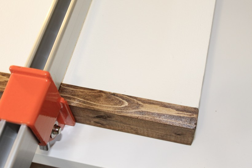 Attaching wood sign frame pieces to sign backing with clamp