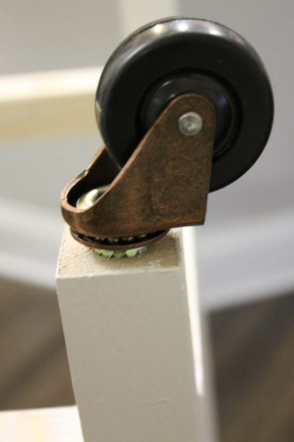 Inserting caster wheels into the bottom of the bar cart frame