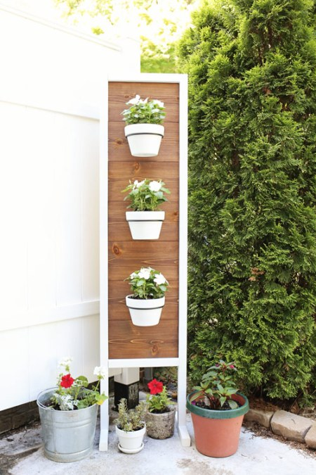 Vertical Planter DIY stand with flowers in front of fence and tree