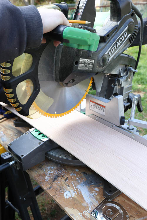 A miter saw cutting shiplap boards to size for shiplap ceiling installation