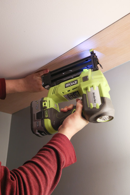 A brad nailer attaching a shiplap plank to the ceiling