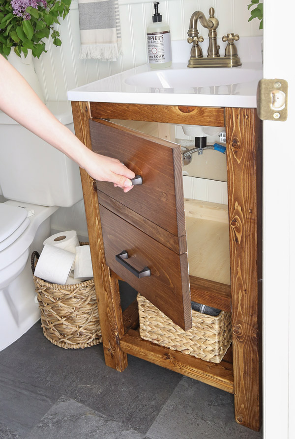 opening a bathroom vanity door with a faux drawer door