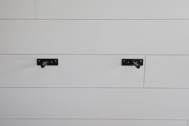 two heavy duty steel floating shelf brackets hung on the wall