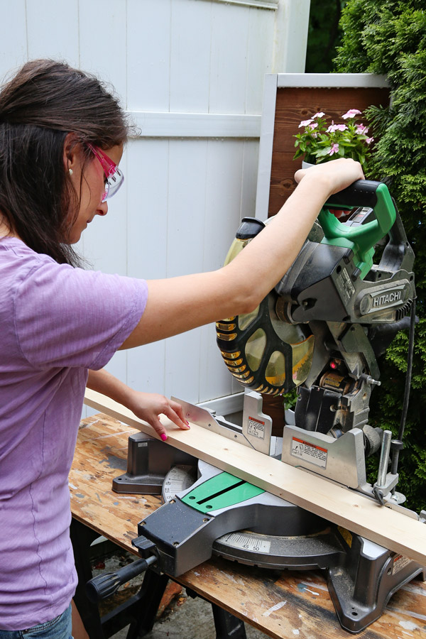 woman using a miter saw with pink saftey glasses