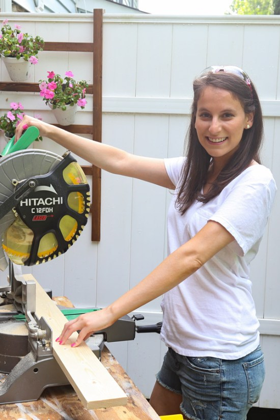 woman woodworking with a miter saw and pink saftey glasses