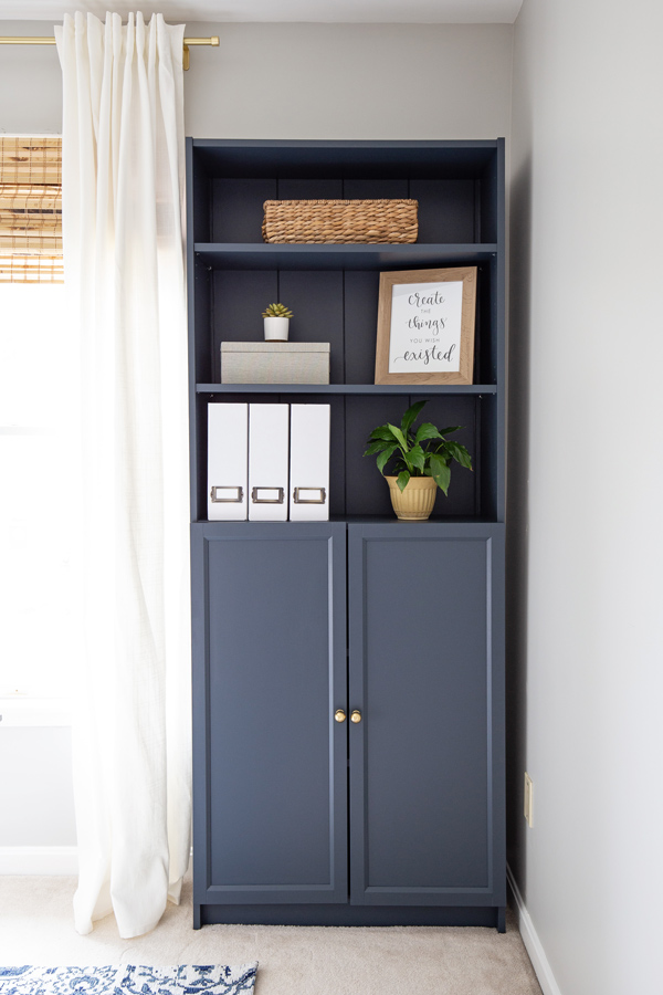 Navy bookcase with styled shelves and decor in a home office