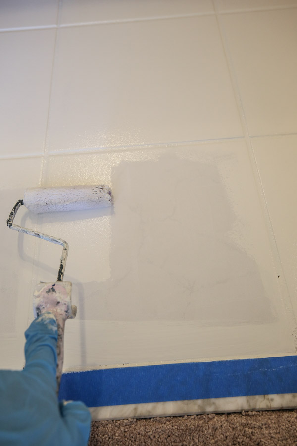 painting ceramic tile floor in a bathroom with a paint roller