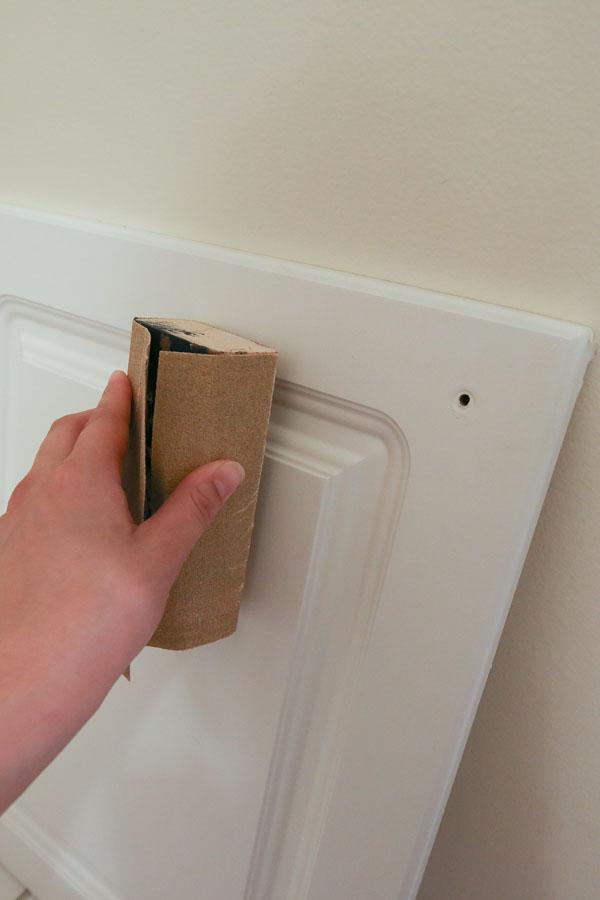hand sanding bathroom vanity doors before painting