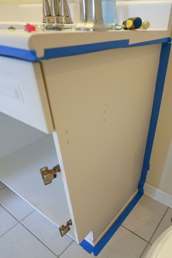 using painters tape to tape off walls and counters before painting bathroom vanity
