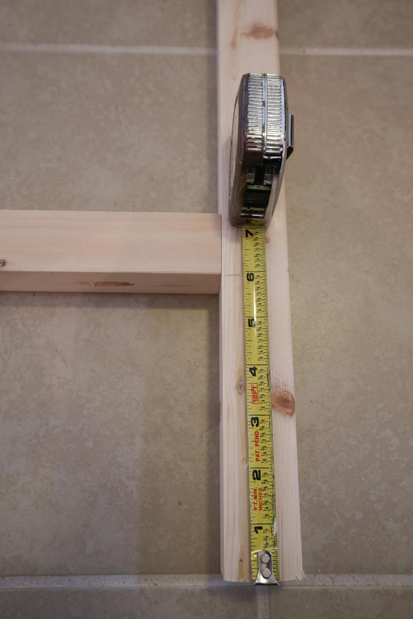 Using a tape measure to measure bottom wood support brace 6 inches up from ground