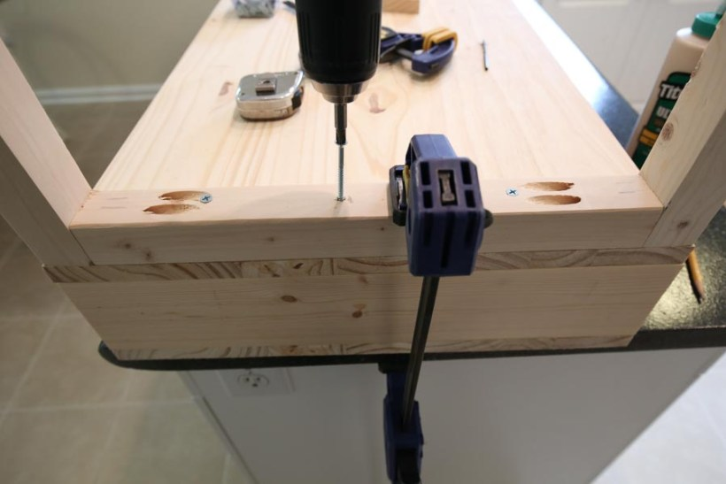 Using a drill and screws to add wood base board to the bottom of the vanity top