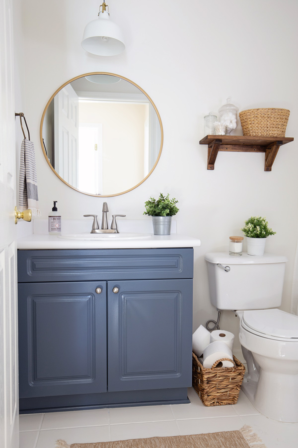 budget bathroom makeover reveal with blue bathroom vanity, white walls, and round gold mirror