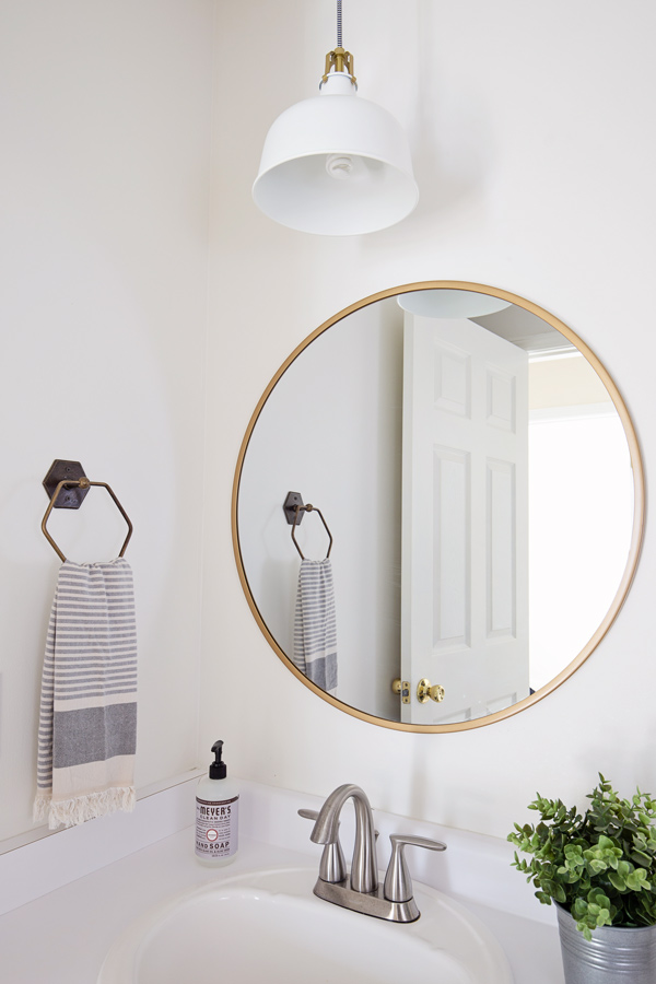 round gold mirror and white and gold pendant light over bathroom sink