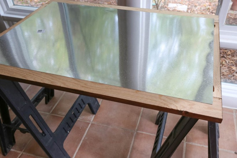 Lining up a large piece of sheet metal over the back of the magnet board wood frame