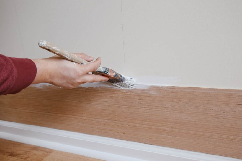 Painting shiplap board gaps during installation with a paint brush