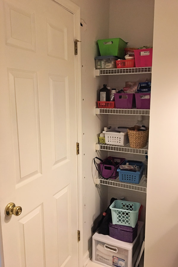 storage nook with shelves behind bathroom door before makeover