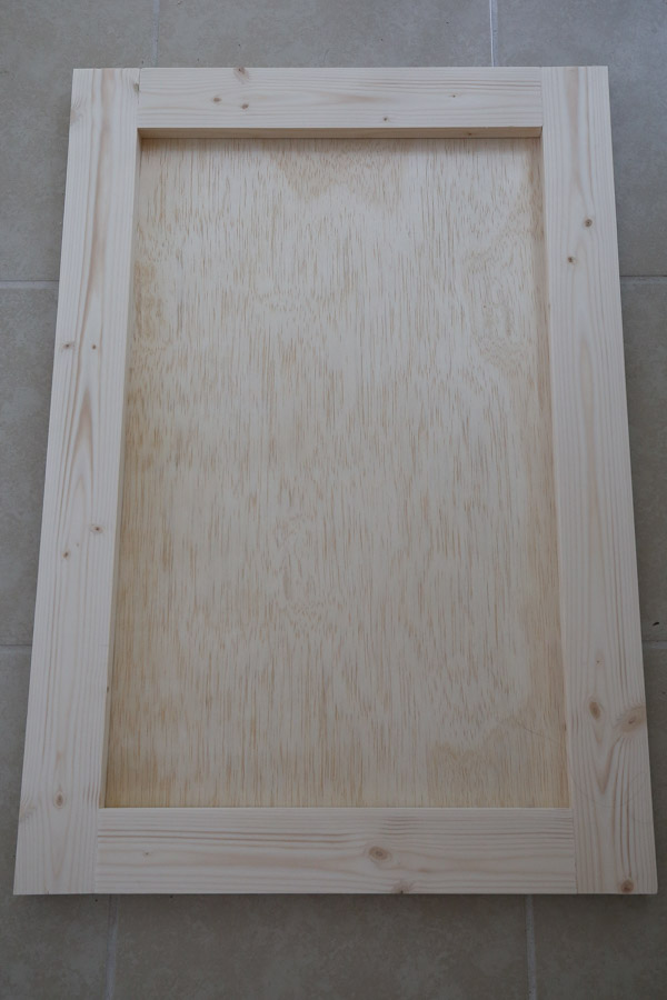 """Attach a piece of 1/4"""" plywood the back of the door frame with screws"""