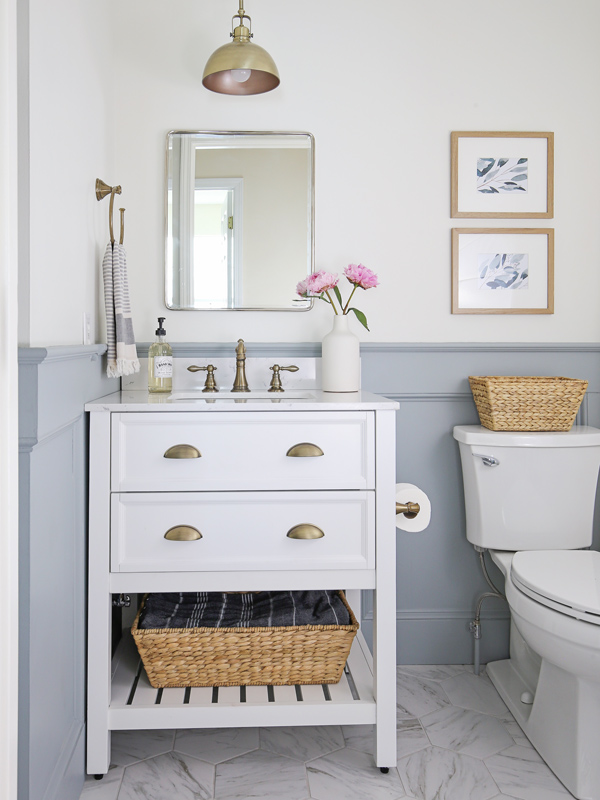 DIY small bathroom makeover with porcelain marble floors, white vanity, and blue gray wainscoting