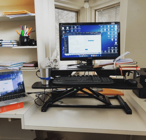 Angela's office showing a desk with a platform to raise/lower her monitor and keyboard so it can become a standing desk.